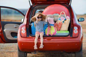 Mädchen mit Gepäck im Kofferraum